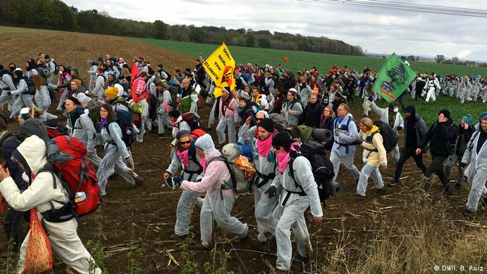 Protesters cross a field during a massive protest against coal in western Germany