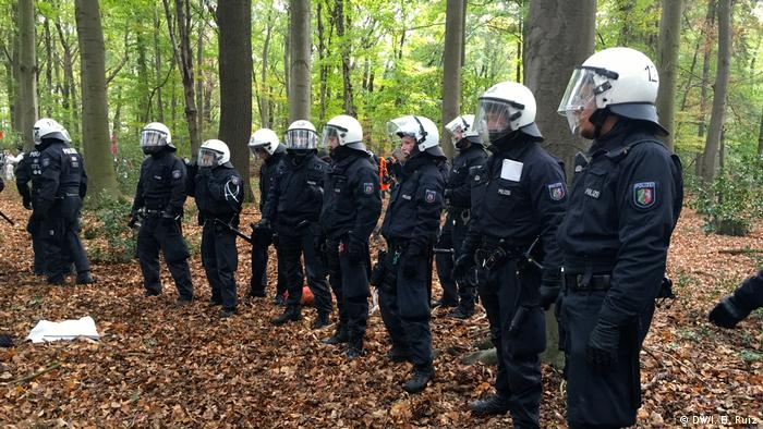 Police officers make a barrier inside the forest during a massive anti-coal protest in western Germany. They prevent protesters from going in that direction