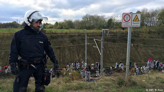 Policejní důstojník stojící na okraji kopce.  Za ním demonstranti dorazili k vlakové lince s uhlím