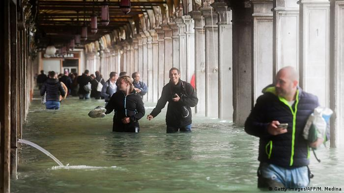 Tourists under arches next to the flooded St Mark's Square