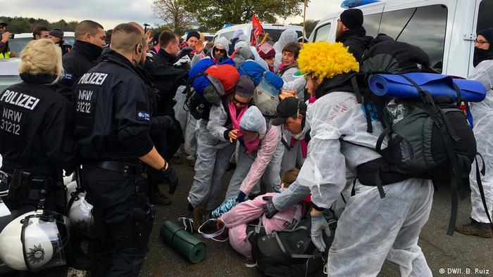 Demonstrant po pádu ležel na zemi.  Ostatní policisté jí pomohli vstát, zatímco policisté se dívali