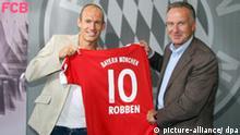 Der Neuzugang des FC Bayern München, Arjen Robben (l) posiert am Freitag (28.08.2009) in München mit dem Vorstandsvorsitzenden von Bayern München, Karl-Heinz Rummenigge, und seinem neuen Trikot. Foto: Bayern München dpa/lby +++(c) dpa - Report+++