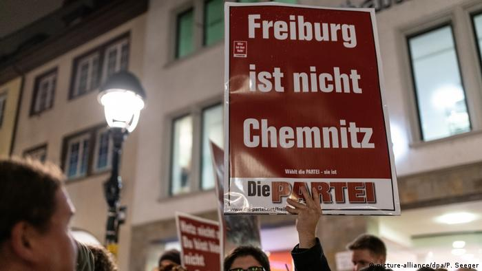 A counterprotester holds a placard that reads: Freiburg is not Chemnitz