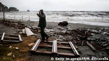 A man gestures as he walks aside garbages on the beach of Monterosso al Mare, village in the Liguria region, on October 29, 2018 - Ahead of bad weather with wind gusts up to 100 km/h on the coast and 150 km/h in the mountains, and a total of precipitation in a few days equivalent to the rainfall of several months, Italy was on the red alert in the northern regions and orange over a good part of the rest of the peninsula. (Photo by Marco BERTORELLO / AFP) (Photo credit should read MARCO BERTORELLO/AFP/Getty Images)