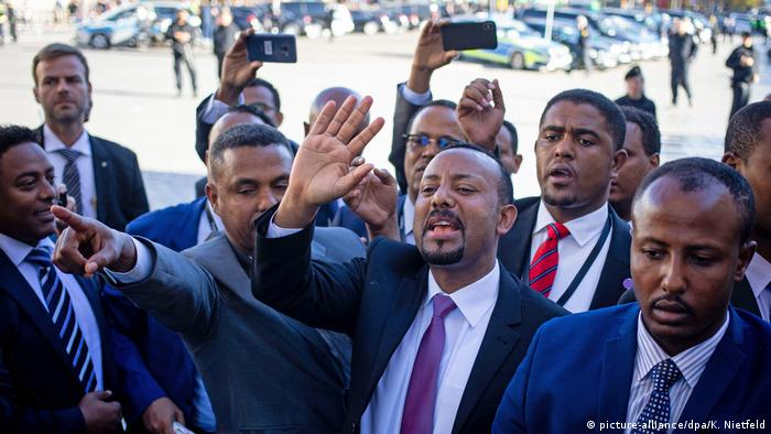 Ethiopian Prime Minister Abiy Ahmed surrounded by security personnel and waving to followers