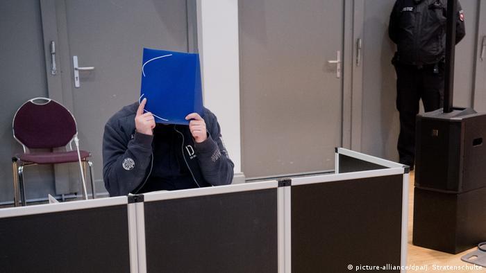 O enfermeiro alemão Niels H. esconde o rosto ao chegar ao tribunal em Oldenburg, no noroeste da Alemanha