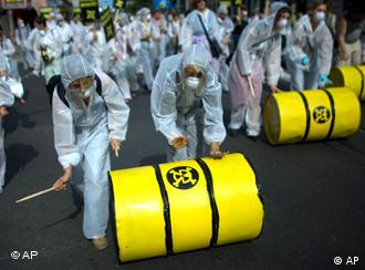Protesters in gas masks and body suits rolling a 'radioactive' drum