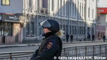 A Russian policeofficer patrols in a street near a building housing the FSB security service in Arkhangelsk on October 31, 2018, after an explosive device went off inside the building. - Russian authorities said they have opened a terrorism investigation after a bombing on October 31 by a 17-year-old local resident at a building housing the FSB security service in the north of the country. (Photo by Michail SHISHOV / AFP) (Photo credit should read MICHAIL SHISHOV/AFP/Getty Images)