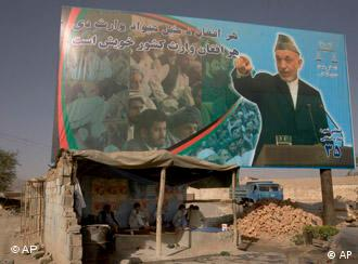 Afghan men in a shop dwarfed by a poster of Hamid Karzai in Kabul