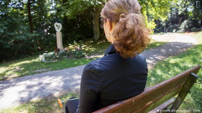 صورة لامرأة جالسة تتأمل قبرا
