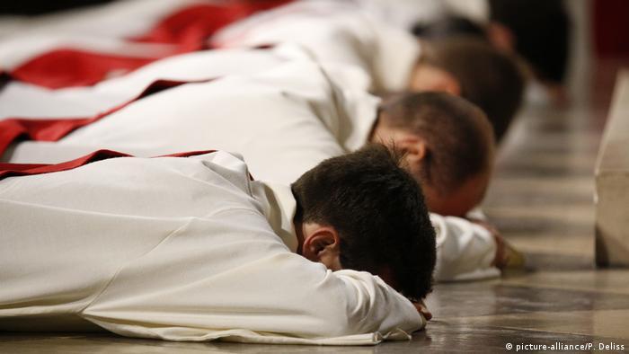 Vier junge Männer, die zu Priestern geweiht werden, liegen in liturgischen Gewändern auf dem Kirchenboden