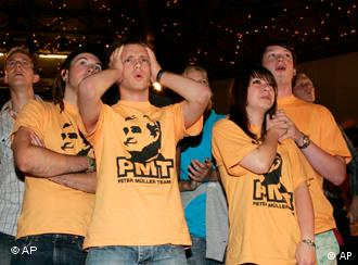 Supporters of Merkel's CDU party react after projections point to heavy losses in Saarland and Thuringia