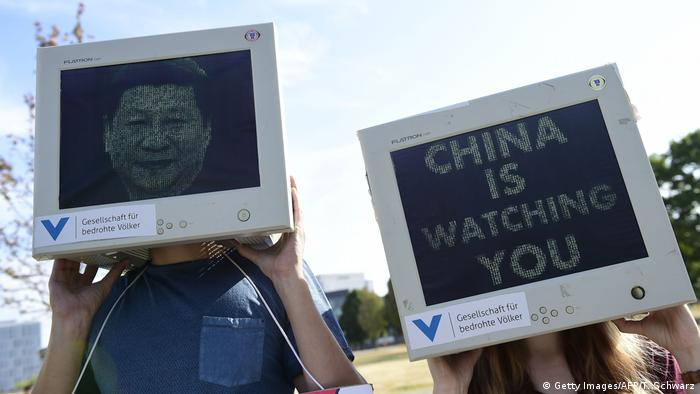 Protesters wear computer monitors with Chinese President Xi Jinping's face and the phrase China is watching you during a demonstration in Berlin, Germany