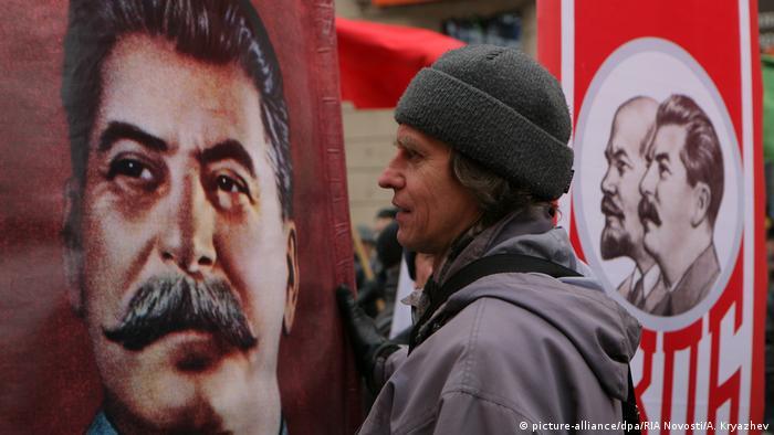 Мужчина рядом с портретом Сталина