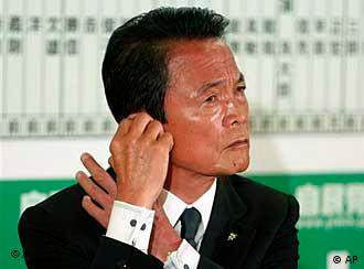 Prime Minister Taro Aso, leader of the Liberal Democratic Party, adjusts a earpiece during a TV interview while observing the result of the parliamentary elections ballot counting at the party headquarters in Tokyo Sunday, Aug. 30, 2009. Aso conceded defeat in elections Sunday as media exit polls indicated the opposition had won by a landslide, sending the conservatives out of power after 54 years of nearly unbroken rule amid widespread economic anxiety and desire for change. (AP Photo/Shuji Kajiyama)
