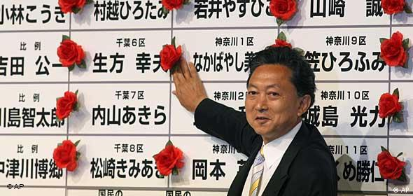 Yukio Hatoyama, leader of the main opposition Democratic Party of Japan, adds a red rosette on the name of a winner candidate as he observes the ballot counting of parliamentary elections at the party's election center in Tokyo, Japan, Sunday, Aug. 30, 2009. The left-of-center Democratic Party was set to win 300 or more of the 480 seats in the lower house of parliament, ousting the Liberal Democrats, who have governed Japan for all but 11 months since 1955, according to exit polls by all major Japanese TV networks. (AP Photo/Koji Sasahara)
