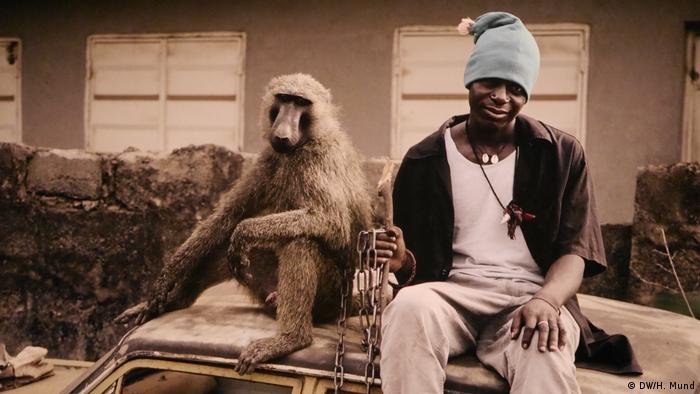 man with a chained monkey sits on a car