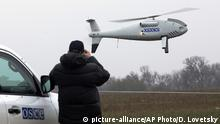 FILE - In this Thursday, Oct. 23, 2014 file photo, a member of the Organization for Security and Co-operation in Europe (OSCE) mission to Ukraine watches a drone take off during a test flight near the town of Mariupol, eastern Ukraine. Germany and France say it appears that Russian-backed separatists in Ukraine downed a drone being used by neutral European observers and are demanding accountability. In a joint statement, they said Thursday, Nov. 1, 2018 the downing is a clear violation of the Organization for Security and Cooperation in Europe's Special Monitoring Mission in Ukraine, which is to have unimpeded access. (AP Photo/Dmitry Lovetsky, file)  