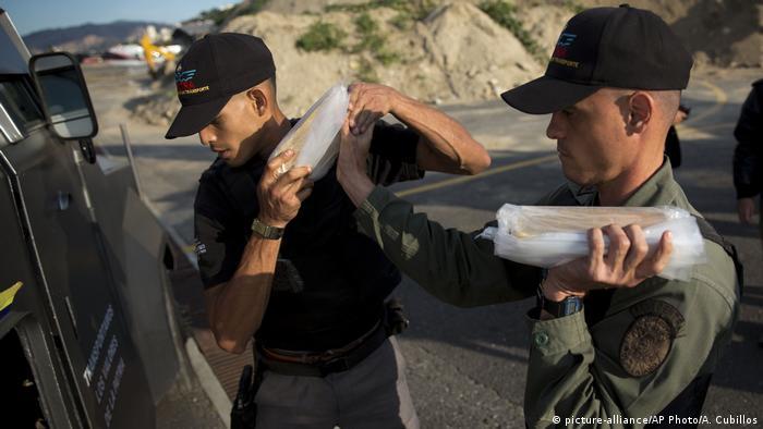 Venezuela'da güvenlik görevlileri Merkez Bankası'na külçe altın taşıyor. ABD Venezuela'nın altın ticaretine yaptırım uygulama kararı aldı