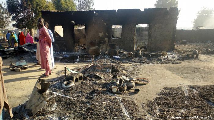 Displaced people stare at the aftermath of a Boko Haram attack in Nigeria (picture-alliance/AP/Jossy Ola)