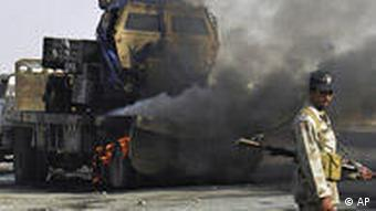 A Pakistani paramilitary soldier stands next to a burning truck, loaded NATO supplies in August 2009.