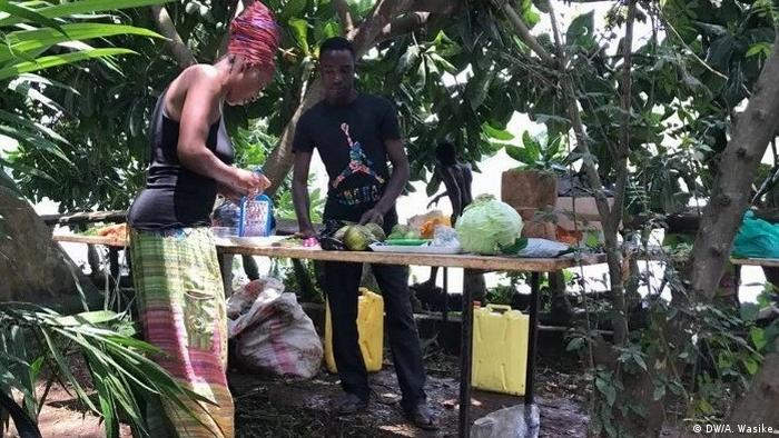 A man and a woman in a pink headwrap stand over a table laden with vegetables under a few trees