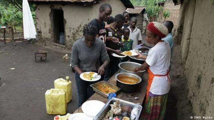 A woman dishes out food from metal pots for a group of people queing at an outdoor counter