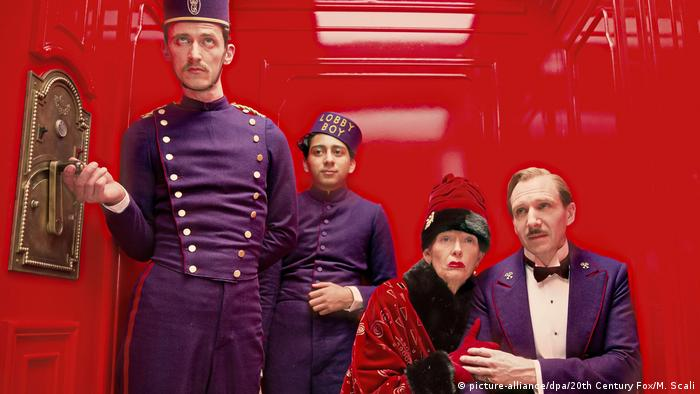 Swinton dressed in a red robe as an old woman in an elevator surrounded by bellboys in a still from The Grand Budapest Hotel (picture-alliance/dpa/20th Century Fox/M. Scali)