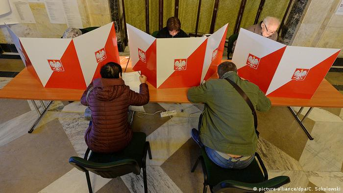 Two people voting at a polling station in Poland