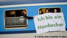 Czech activists hold up a banner from a train window: Ich bin ein Hambacher