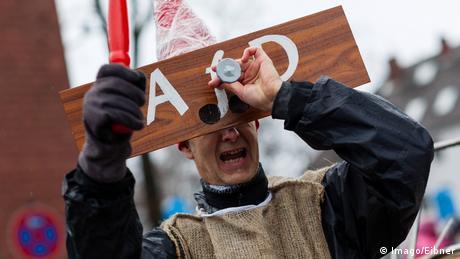 Ein Mann trägt beim Karneval ein Brett vor dem Kopf mit der aufschrift AfD
