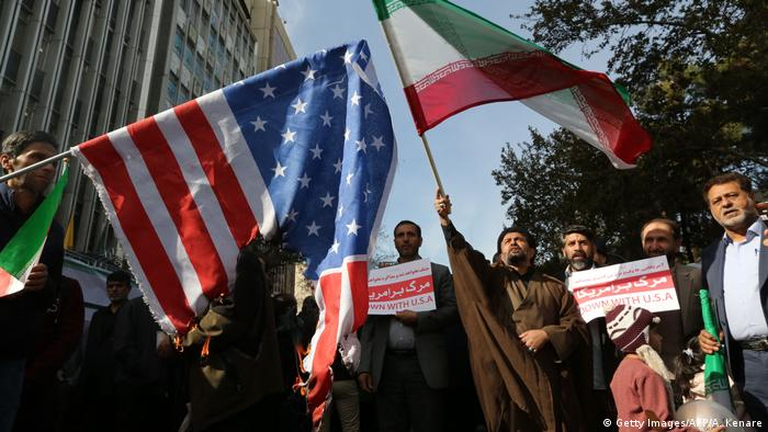 Protesters in Tehran burn a US flag, hold signs and wave an Iranian flag