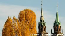 05.11.2018, Bayern, Nürnberg: Bäume mit herbstlich gelbgefärbten Blättern stehen vor der Kulisse der Türme der Kirche St Lorenz. Foto: Daniel Karmann/dpa +++ dpa-Bildfunk +++ | Verwendung weltweit
