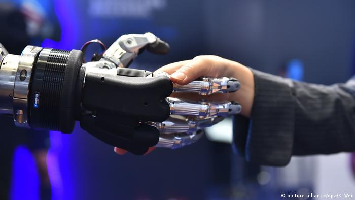 Robotics hand shaking hands with a human hand at an International Import Expo (picture-alliance/dpa/K. Wei)