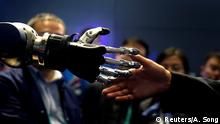 A man tries to shake hands with SCHUNK 5-finger anthropomorphic gripper hand during the China International Import Expo (CIIE), at the National Exhibition and Convention Center in Shanghai, China November 6, 2018. REUTERS/Aly Song
