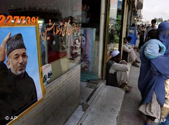 Afghan woman with child walks by poster of President Hamid Karzai in Kabul