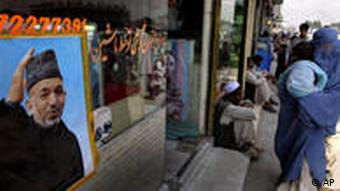 A woman in Kabul in front of a Hamid Karzai poster