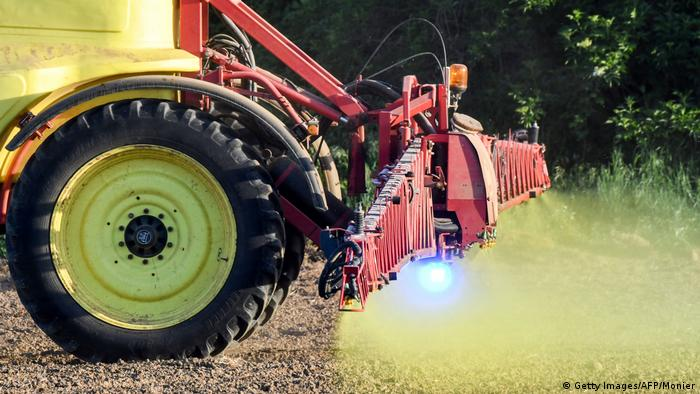 A tractor sprays a neon yellow pesticide on farmland