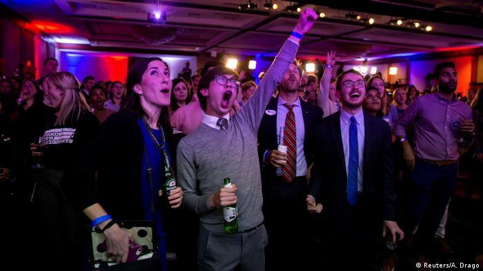 People cheer as they watch election results come in at a Democratic election night rally