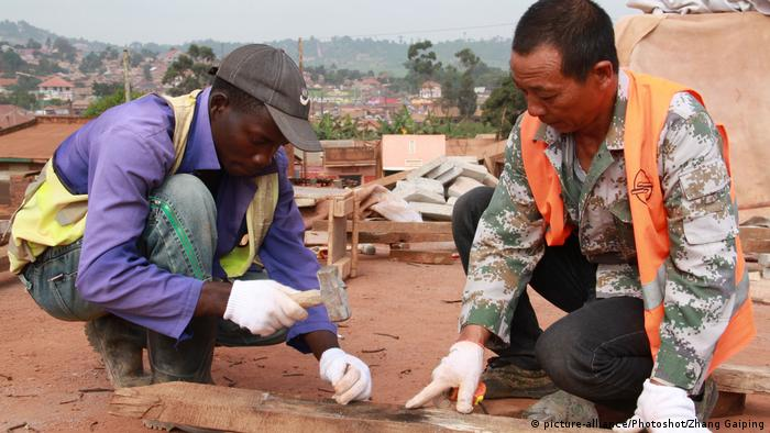 A Ugandan worker and a Chinese man hammering nails into a wooden beam