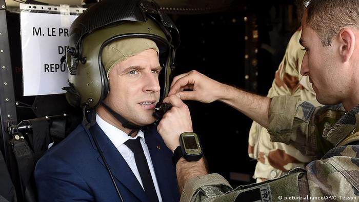 A French soldier adjusts the helmet of French President Emmanuel Macron