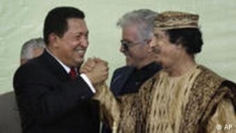 Venezuelan President Hugo Chavez, left, grasps the hand of Libyan Leader Moammar Gadhafi, right, at the Special Session of the African Union Assembly on the Consideration and Resolution of Conflicts in Africa, in Tripoli, Libya, Monday, Aug. 31, 2009. The Libyan leader Moammar Gadhafi blamed much of Africa's violence on what he described as intervention by unnamed foreign powers, bent on plundering Africa's natural resources. (AP Photo/Ben Curtis)