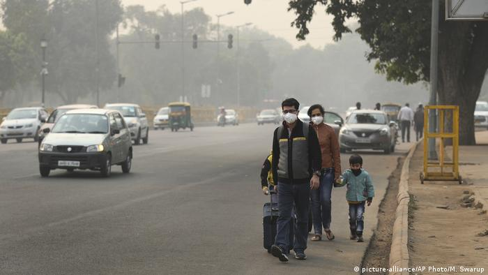 A family wears pollution masks and walk looking for a transportation a day after Diwali festival, in New Delhi (picture-alliance/AP Photo/M. Swarup)