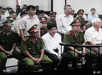 A TV screen set up in a media room in courthouse, shows Vietnamese journalists Nguyen Van Hai of Tuoi Tre (Youth) newspaper, back left, Nguyen Viet Chien of Thanh Nien newspaper, back right, and also two police officers Dinh Van Huynh, front second from left, and Pham Xuan Quac, front right, during their trial in Hanoi,Vietnam, Tuesday, Oct. 14, 2008. Two Vietnamese journalists went on trial Tuesday in Hanoi for allegedly writing false information in reports about one of the country's most high-profile corruption cases. Two police officers who allegedly provided information to the two journalists also went on trial Tuesday on charges of deliberately revealing state secrets. (AP Photo/ Vu Tien Hong)