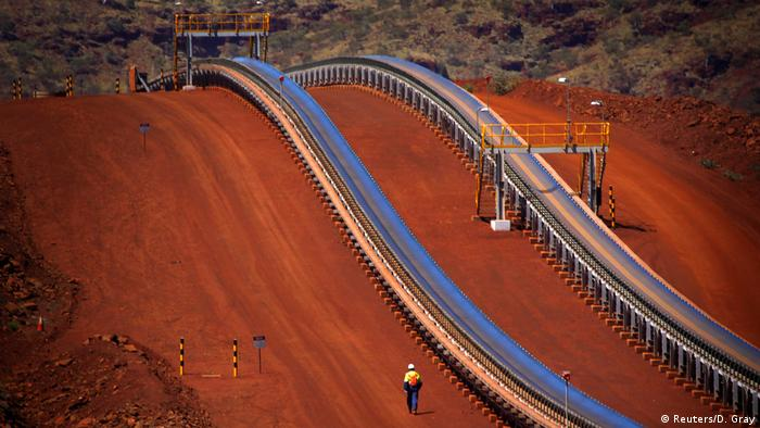 A worker walks near conveyer belts loaded with iron ore at the Fortescue Solomon iron ore mine located in the Valley of the Kings in Australia