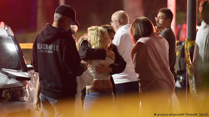 People comfort each other as they stand near the scene Thursday, Nov. 8, 2018, in Thousand Oaks, Calif
