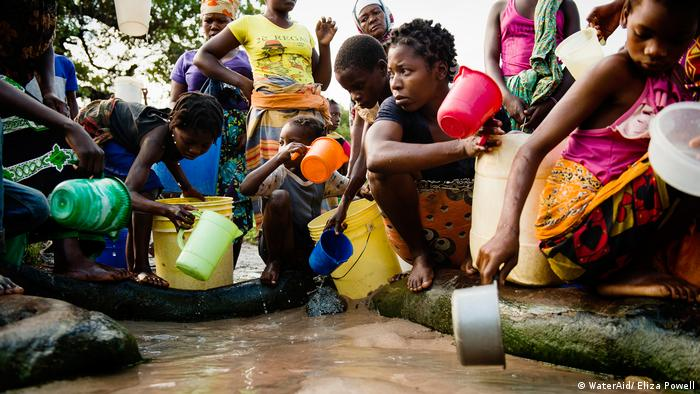 Women and children collect water in Mozambique