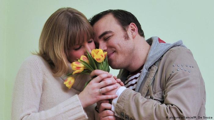 A man and a woman smell a bunch of flowers together