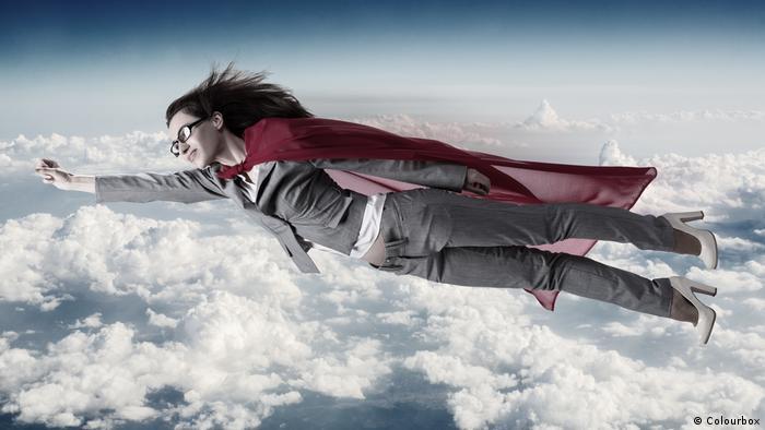 Eine Frau fliegt mit erhobener Faust und Umhang über den Wolken (Colourbox)