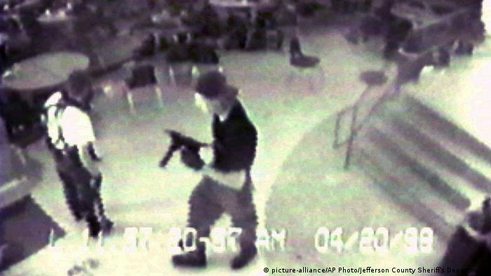 Eric Harris, left, and Dylan Klebold, carrying a TEC-9 semi-automatic pistol, are pictured in the cafeteria at Columbine High School